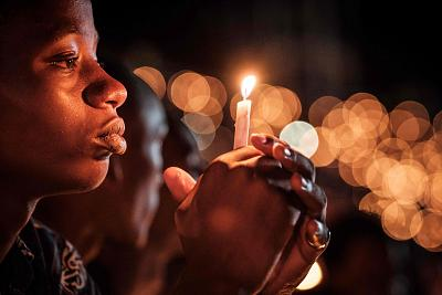 A person holds a candle during a night vigil and prayer at Amahoro Stadium to remember the victims of the 1994 Rwandan genocide in Kigali on April 7, 2019.