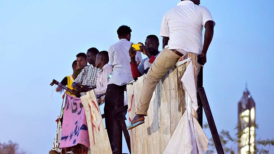 Image: Protesters sit on a torn billboard in Khartoum, Sudan