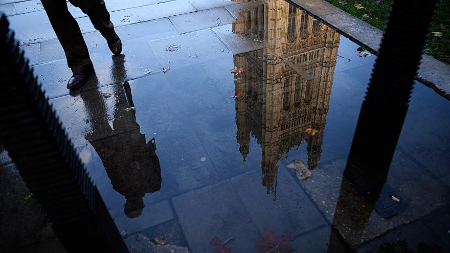 Image: The Houses of Parliament is reflected in an puddle in London, Englan