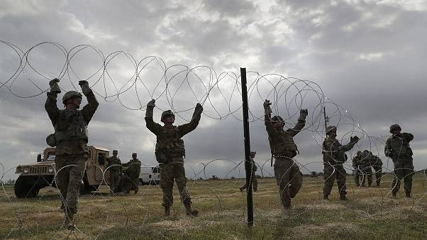 U.S. Army soldiers from Ft. Riley, Kansas string razor wire near the port o