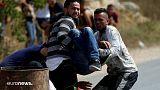 جوانان فلسطینی یک زخمی را از میدان دور میکنند