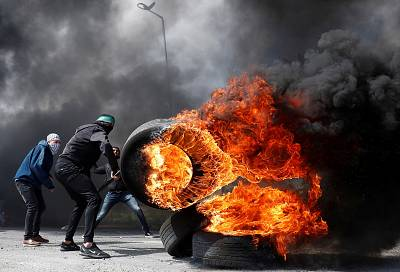 A Palestinian protester moves a burning tire during clashes with Israeli troops near the Jewish settlement of Beit El in the West Bank on March 27.