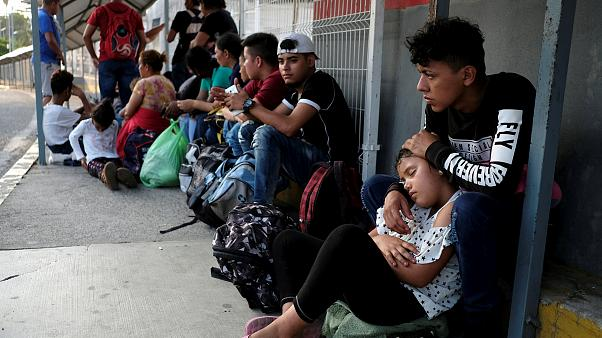 Image: Migrants from Honduras wait on the border bridge between Mexico and