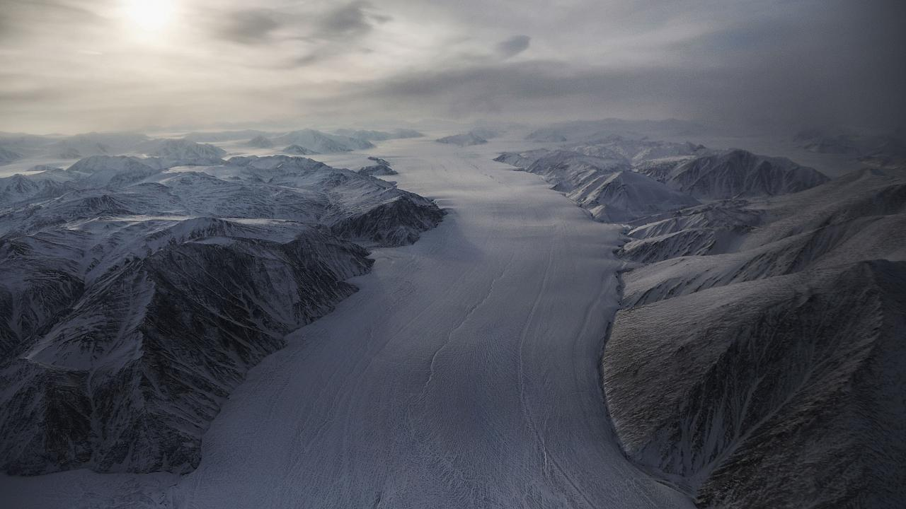 A section of glacier flows between ridges on Ellesmere Island, Canada.