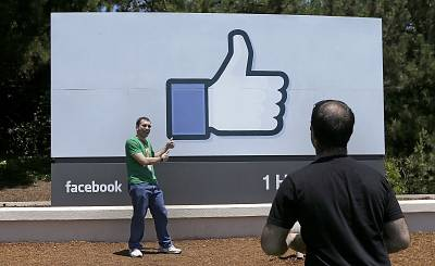A man poses for photos in front of the Facebook sign on the company\'s campus in Menlo Park, California, in 2014.