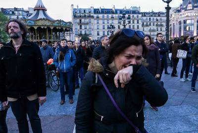 A woman weeps as Notre Dame Cathedral in Paris is engulfed in flames on Monday.