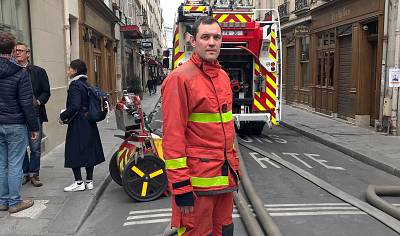 A firefighter stands next to his truck in Paris on Tuesday.