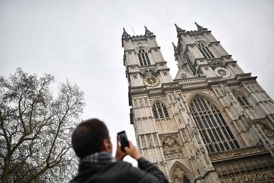 A tourist takes a photograph of Westminster Abbey on Tuesday.