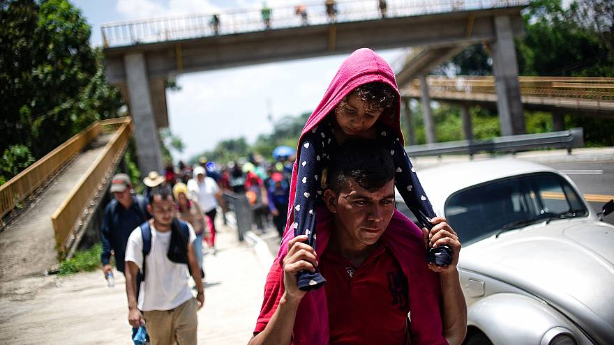 Image: Central American migrants traveling with a caravan rest on a road be