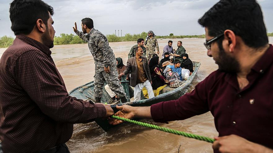 Image: Iranian soldiers help civilians in a flooded village near the city o