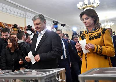 Ukrainian President Petro Poroshenko (L) and his wife Maryna Poroshenko hold their ballot papers into a ballot box at a polling station during the second round of Ukraine\'s presidential election in Kiev on Sunday.