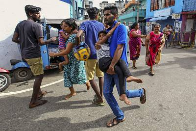 People living near St. Anthony\'s Shrine run for safety after police found explosive devices in parked vehicles, which later exploded in Colombo, Sri Lanka, on Monday.