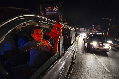 People used their mobile phones at the Francisco Fajardo highway, where they could get telephone service, during a partial power failure in Caracas, Venezuela, on March 9.