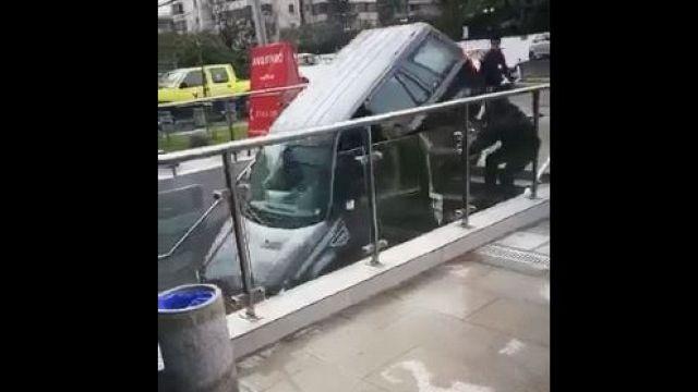 شاهد: سيدة تفر وتنجو بثوان قبل إنزلاق سيارتها وتحطمها
