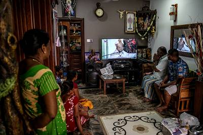 A family watches a televised mass led by Cardinal Malcom Ranjith, a week after a series of bomb attacks at churches, in Colombo, Sri Lanka, on April 28, 2019.