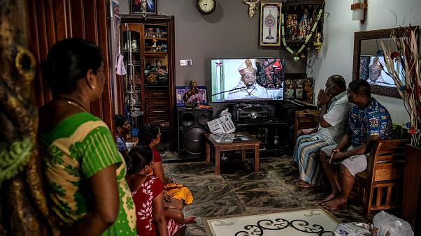 Image: A family watches a televised mass led by Cardinal Malcom Ranjith, a