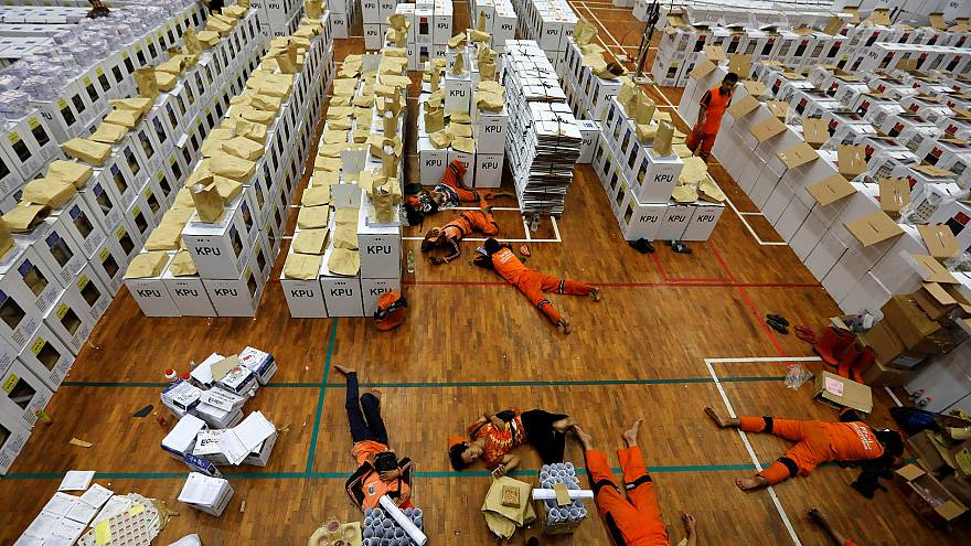 Image: Workers lay during a break as they prepare election materials in a w