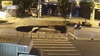 Watch: Phone-watching motorcyclist falls into sinkhole