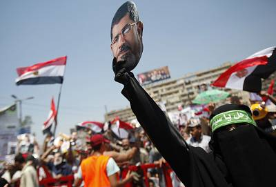 A supporter of the Muslim Brotherhood holds a mask of ousted Egyptian President Mohamed Morsi during a rally around Rabaa Adawiya square in Cairo on July 26, 2013.