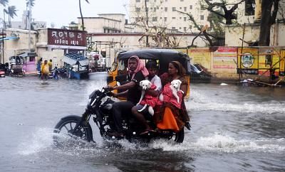 Indian residents ride on a bike along a flooded road after Cyclone Fani landfall in Puri, in the eastern Indian state of Odisha on May 3, 2019.