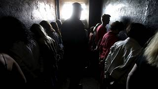 Image: People line up facing the walls as they attend a voluntary imprisonm