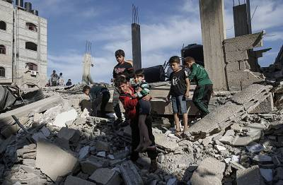 Palestinian children stand atop the remains of a building that was destroyed during an Israeli air strike on Rafah in the southern Gaza strip on Sunday.