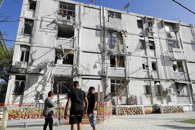 Residents gather in front of a building that was damaged during a rocket strike on the southern Israeli city of Ashkelon near the Gaza border.