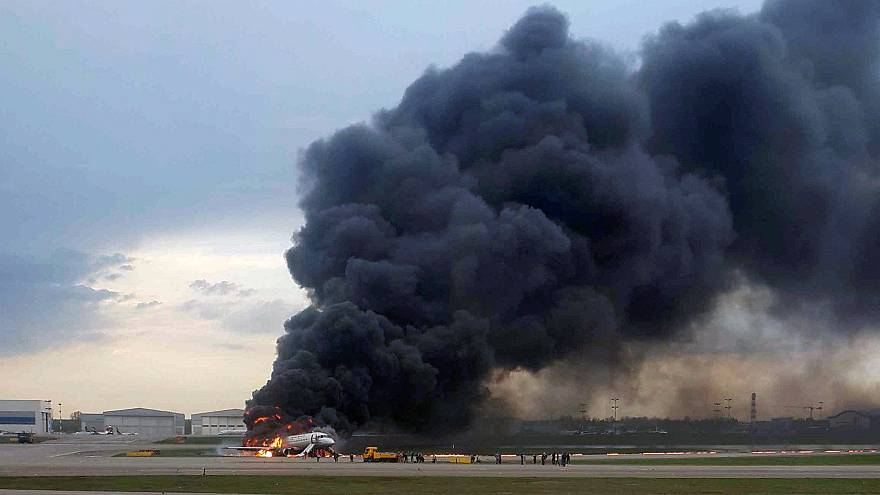 Image: A passenger plane is seen on fire after an emergency landing at the