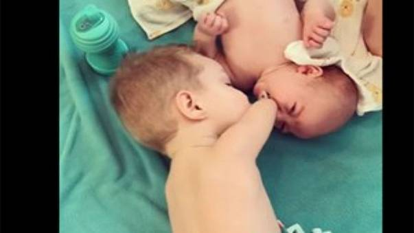 طفل فاقد لذراعيه يساعد أخاه الرضيع