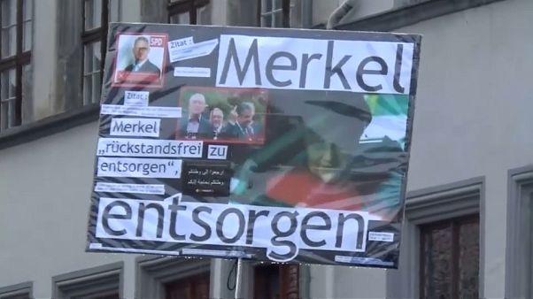 Abucheos y tomates contra Merkel