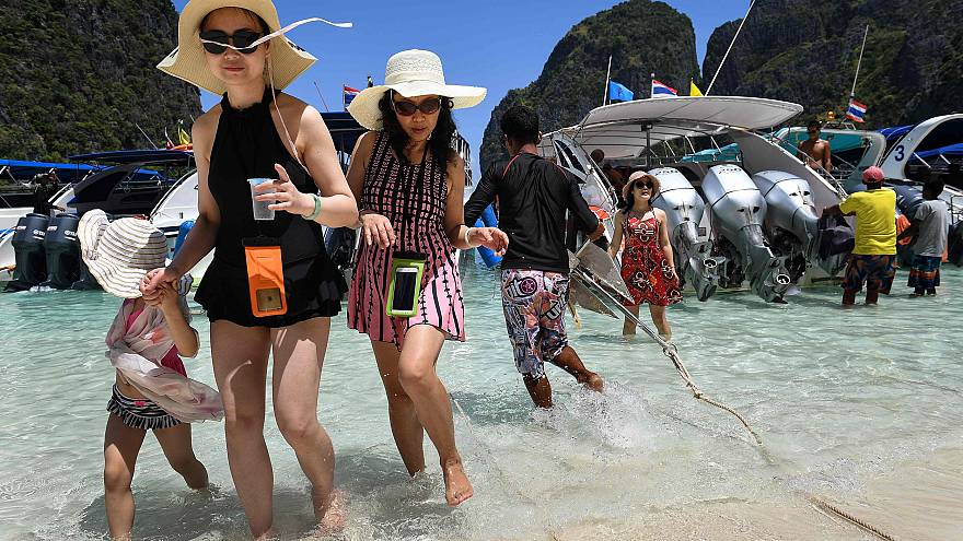 Image: Tourists get off a speedboat onto Maya Bay, on the southern Thai isl