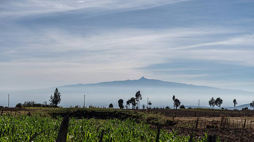 Image: Mt. Kenya peeks out from the clouds beyond a small farm in Embaringo