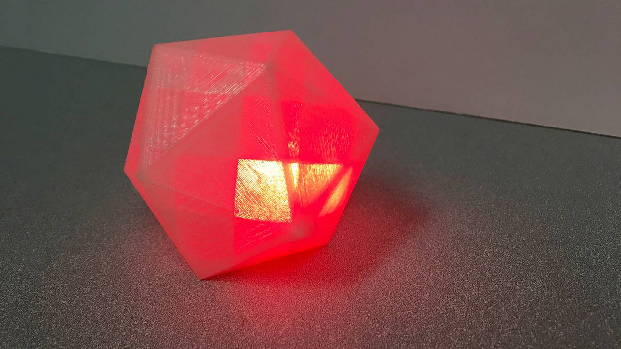 Image: A block-like geometric shape that emits a glowing red light when it