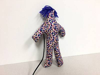 A doll-like fabric body with blue hair provokes users with an irritating laugh until they hit it into submission.