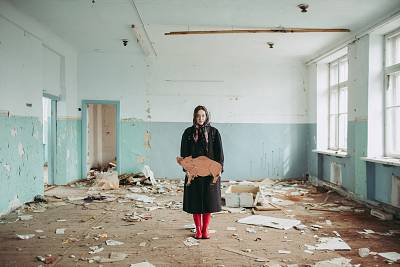 Alisa Gorshenina poses with a cardboard boar she found in an abandoned school in Yakshina, Russia.