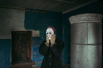 Artist Alisa Gorshenina in an abandoned house in Yakshina, Russia.