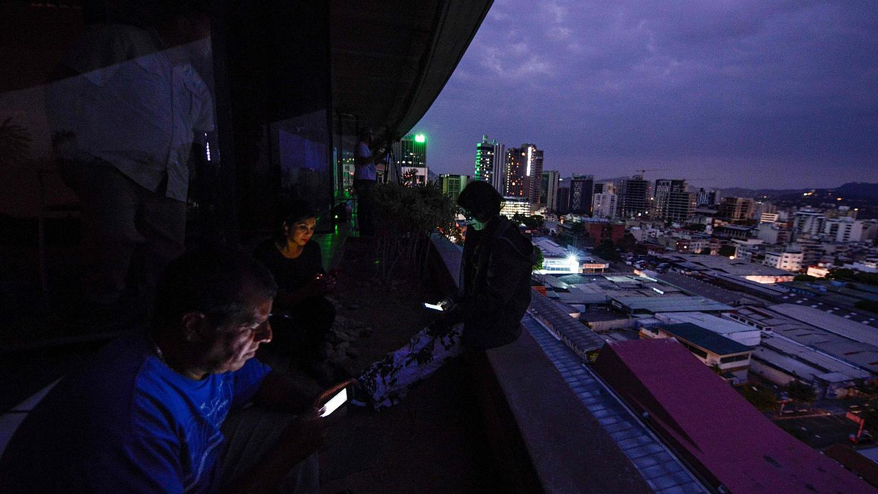 Image: Journalists use their smartphones during a power cut in Caracas, Ven
