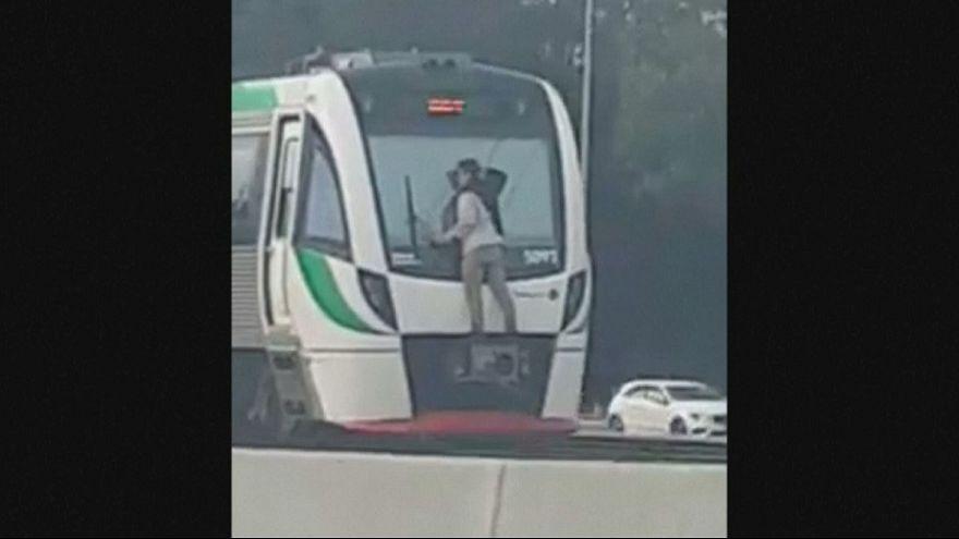 Australien: Mann fährt außen am Zug mit