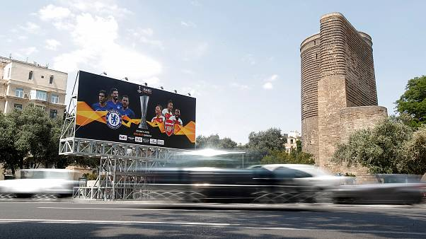 Image: A billboard next to The Maiden Tower in Baku, Azerbaijan