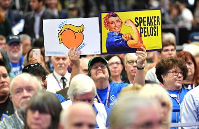 A woman holds up signs as US Speaker of the House Nancy Pelosi takes the stage during the 2019 California Democratic Party State Convention at Moscone Center in San Francisco on June 1, 2019.