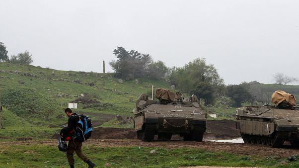 Image: FILE PHOTO: An Israeli soldier walks past armoured Israeli military