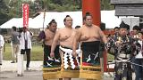 A sumo grand champion performs ring-entering ceremony in Japan