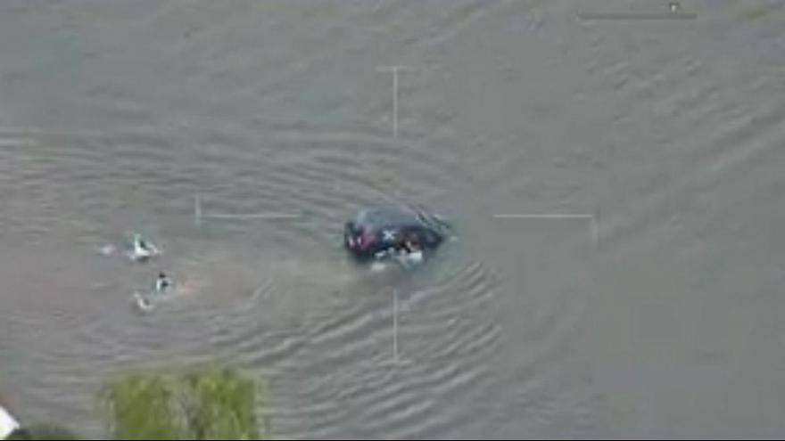 Watch: Police swim out to save woman from sinking car