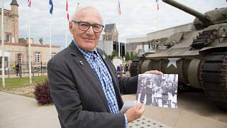 Image: Henry-Jean Renaud holds a photo of himself after the liberation outs