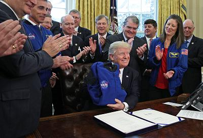 President Donald Trump receives a NASA flight jacket from Chief of the Astronaut Office at NASA Chris Cassidy during a bill signing ceremony in the Oval Office of the White House March 21, 2017.