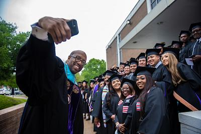 President Michael Sorrell of Paul Quinn College poses with students in Dallas, Texas on May 4, 2019.