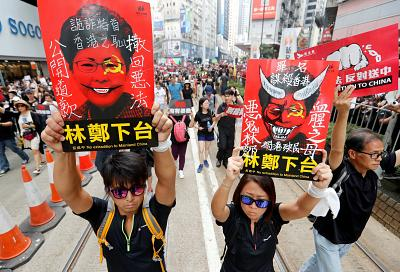 Protesters hold placards with the face of the island\'s chief executive, Carrie Lam.