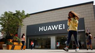 Image: FILE PHOTO: A woman looks at her phone as she walks past a Huawei sh