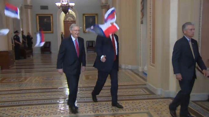 بالفيديو: متظاهر يرمي ترامب بأعلام روسية
