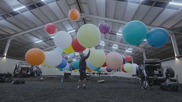 Gökyüzünde 100 balon ve kamp sandalyesinde bir adam